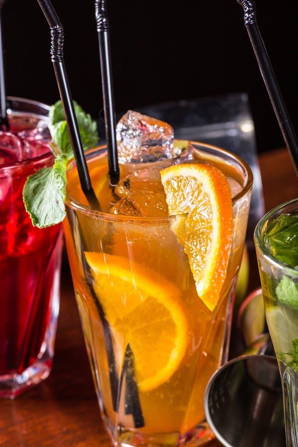 威士忌酒可乐鸡尾酒, mojito鸡尾酒,橙色鸡尾酒,在玻璃玻璃的草莓鸡尾酒与秸杆 酒吧辅助部件:振动器 免版税库存图片