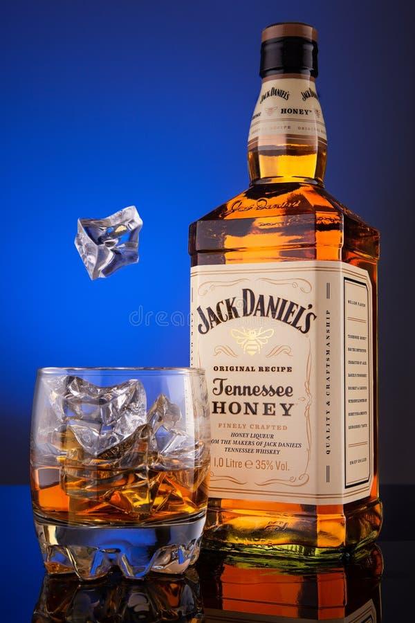 威士忌酒瓶杰克Deniels田纳西蜂蜜原始的食谱和一杯冰 免版税库存照片