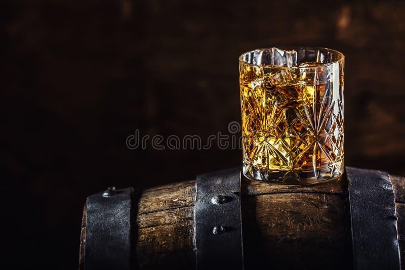 威士忌酒饮料 杯在老木桶的威士忌酒 免版税库存照片