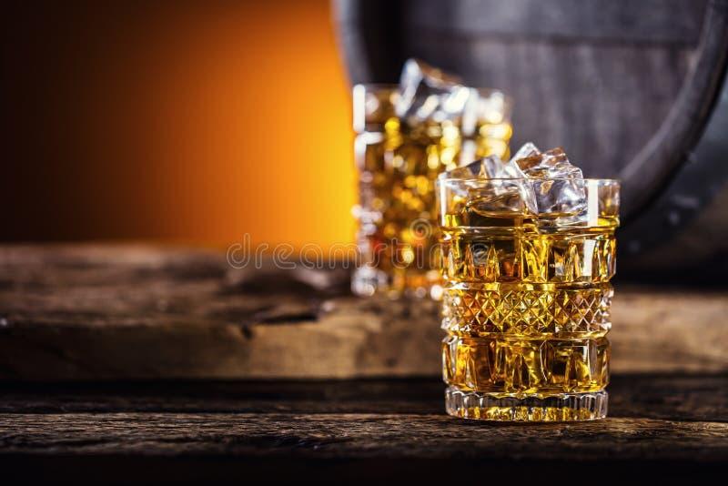 威士忌酒 两个杯子有很多饮料威士忌酒白兰地酒或科涅克白兰地与冰块在减速火箭的样式 老橡木桶在背景中 免版税库存图片