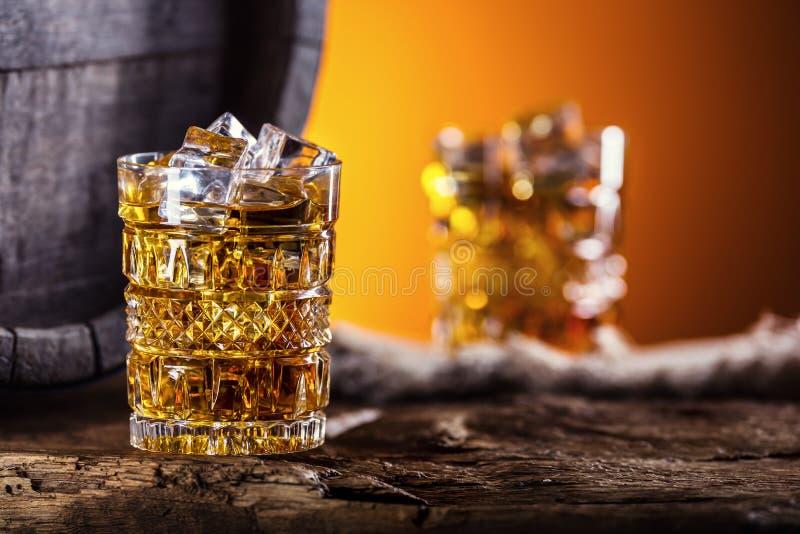 威士忌酒 两个杯子有很多饮料威士忌酒白兰地酒或科涅克白兰地与冰块在减速火箭的样式 老橡木桶在背景中 免版税库存照片