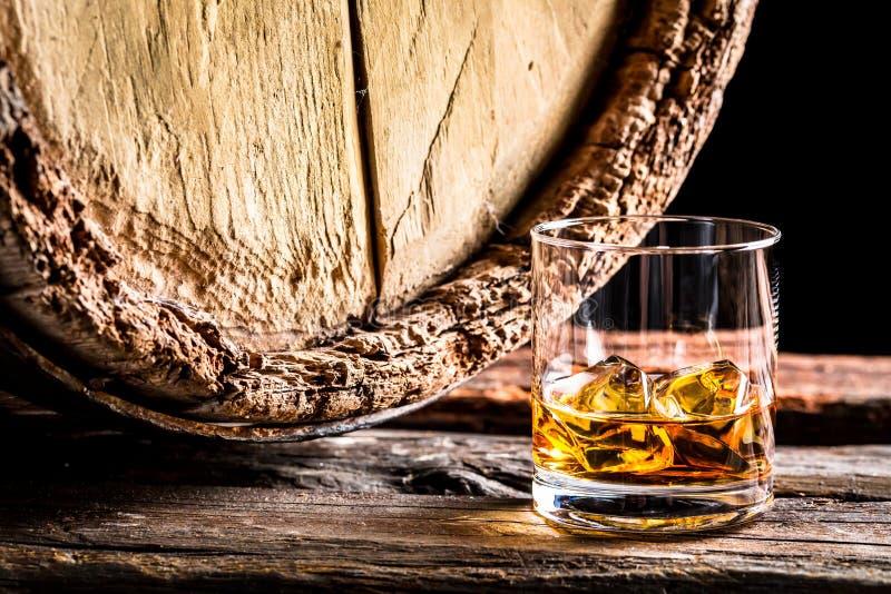 威士忌酒玻璃和老橡木桶 免版税库存照片