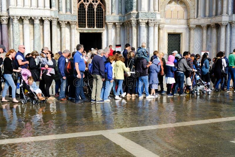 威尼斯、意大利- 2017年9月12日-游人和本机通过被充斥的S做他们的沿圣马尔谷圣殿宗主教座堂墙壁的方式 库存照片