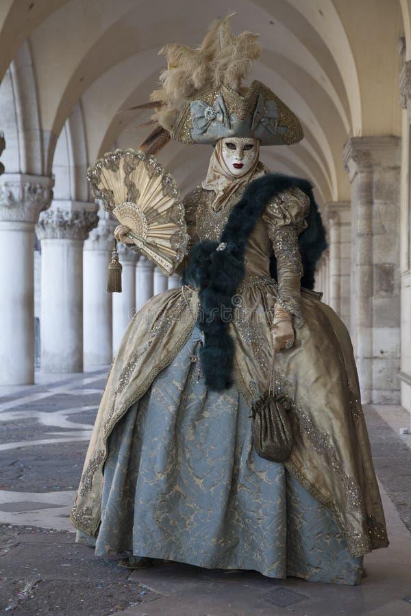 威尼斯在一套五颜六色的服装的狂欢节在共和国总督` s宫殿下威尼斯威尼托意大利欧洲的拱廊的形象和面具 免版税库存照片