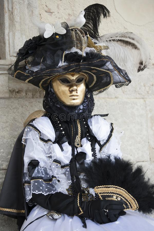 威尼斯在一套五颜六色的黑白服装的狂欢节形象和金子掩没威尼斯意大利 免版税图库摄影
