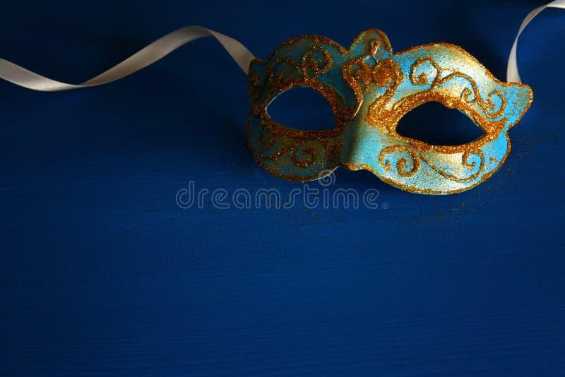 威尼斯式典雅的蓝色和的金子,在蓝色背景的狂欢节面具的图象 免版税库存图片