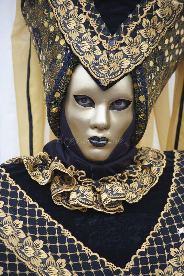 威尼斯式狂欢节服装的人们在一个五颜六色的棕色,黑和金子狂欢节服装和面具威尼斯 免版税库存照片