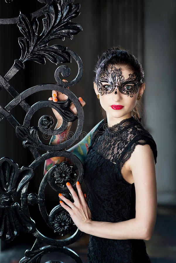 威尼斯式狂欢节面具的神奇妇女在锻铁门附近 免版税图库摄影