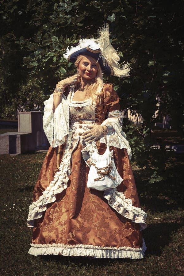 威尼斯式葡萄酒服装的成人白肤金发的妇女 室外 免版税库存照片