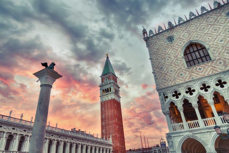 威尼斯标志有红色剧烈的天空的狮子、圣Marco钟楼和共和国总督宫殿在日落期间 举世闻名的威尼斯地标 免版税图库摄影