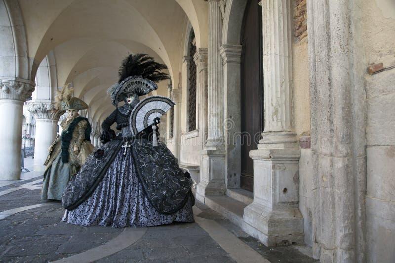 威尼斯狂欢节在图五颜六色的服装和面具在共和国总督` s宫殿下威尼斯的拱廊 免版税图库摄影