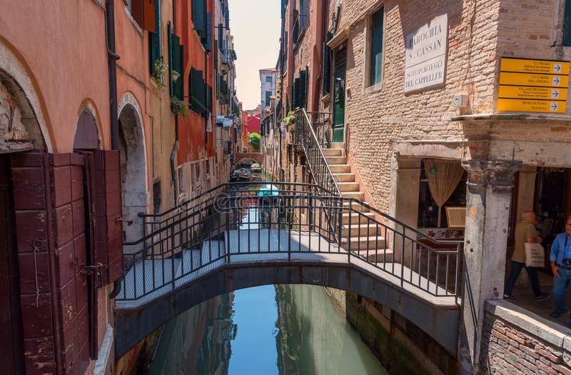 """威尼斯,意大利†""""2017年5月23日:有长平底船和老房子的传统狭窄的运河街道在威尼斯,意大利 免版税库存图片"""
