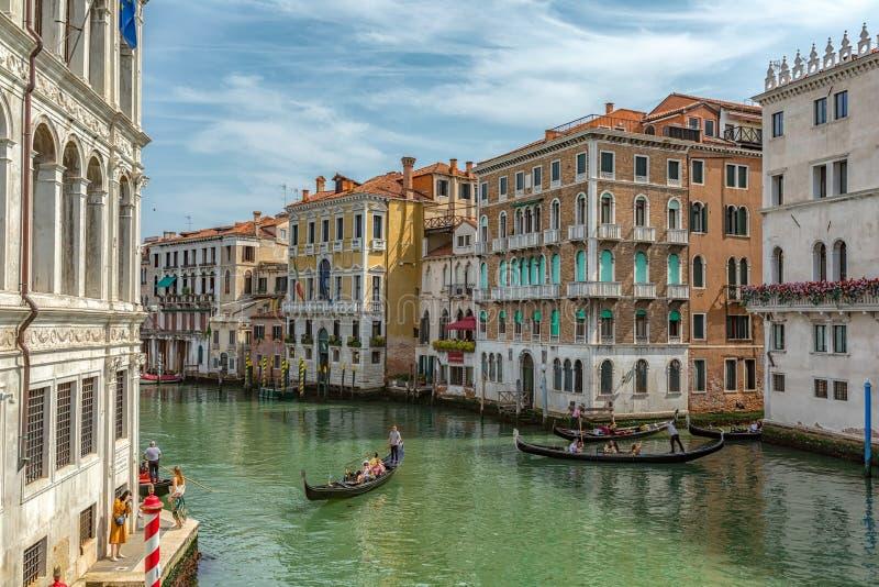 威尼斯,意大利- 12 06 2019年:近长平底船到在大运河街道上的威尼斯大石桥桥梁在威尼斯湾 图库摄影