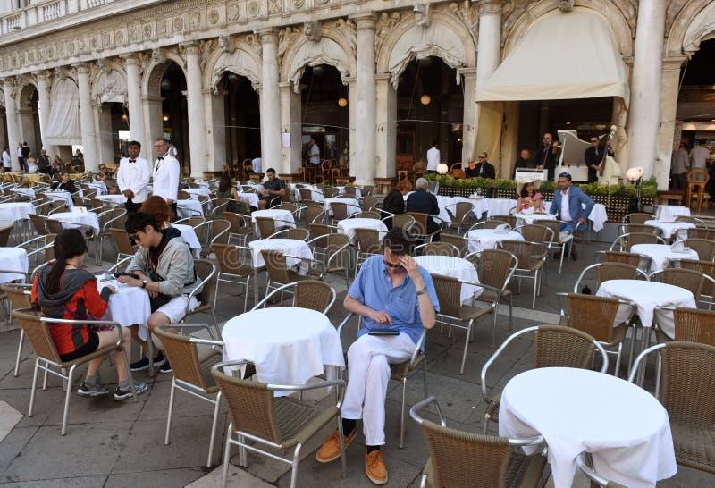 威尼斯,意大利- 2017年6月07日:咖啡馆的人们在圣squar的Marco 免版税库存照片