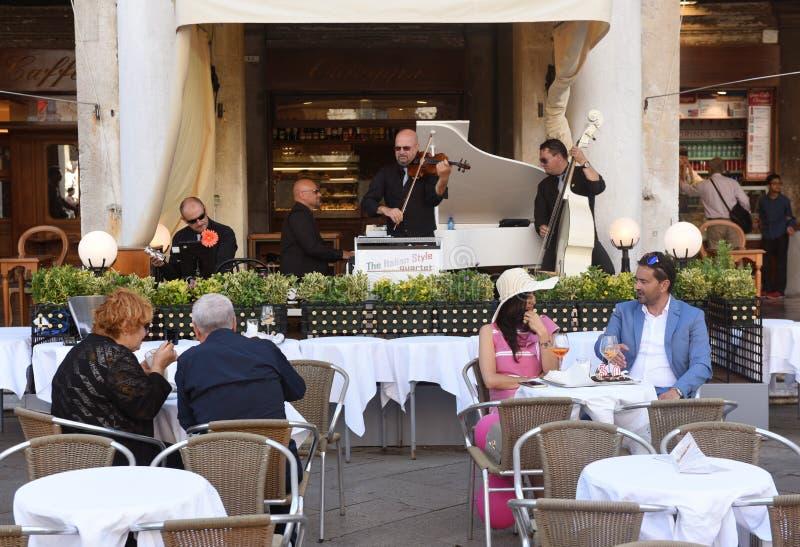 威尼斯,意大利- 2017年6月07日:咖啡馆的人们在圣squar的Marco 库存照片