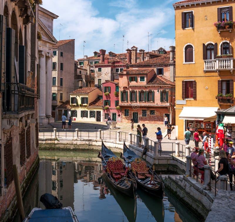 威尼斯,意大利- 2018年5月08日:威尼斯的一个美丽如画的角落 有长平底船的,五颜六色的五颜六色的房子运河 平底船的船夫 库存图片