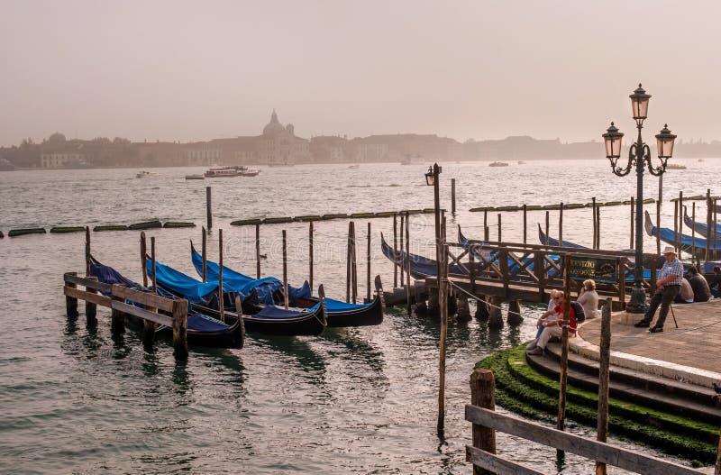 威尼斯,意大利- 2017年10月13日:重创的运河的晚上视图 游人敬佩看法 在前景是 免版税图库摄影