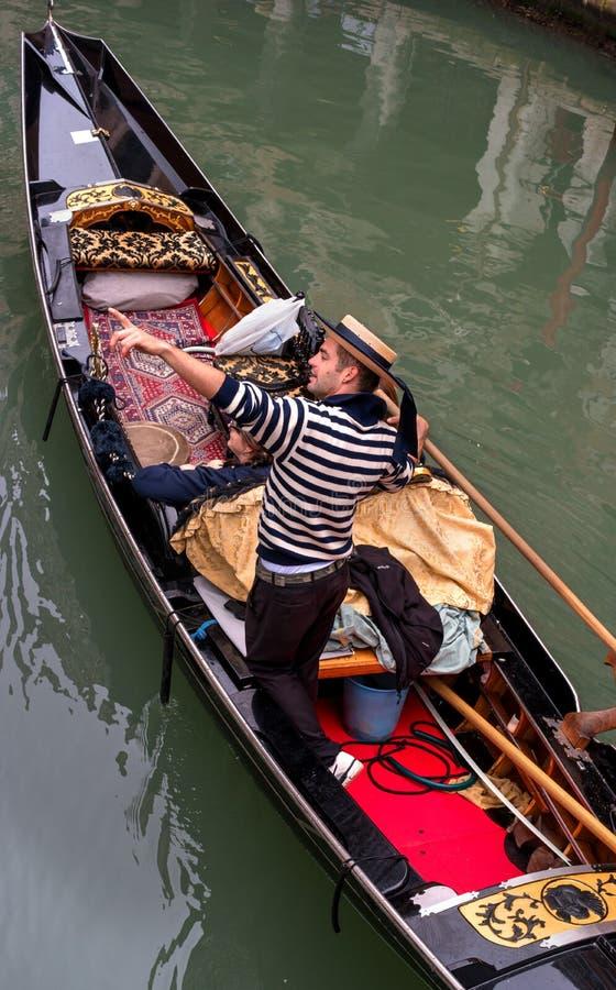 威尼斯,意大利- 2017年10月13日 游人游泳沿一条狭窄的运河的长平底船 对吸引力的平底船的船夫点 的treadled 免版税库存图片