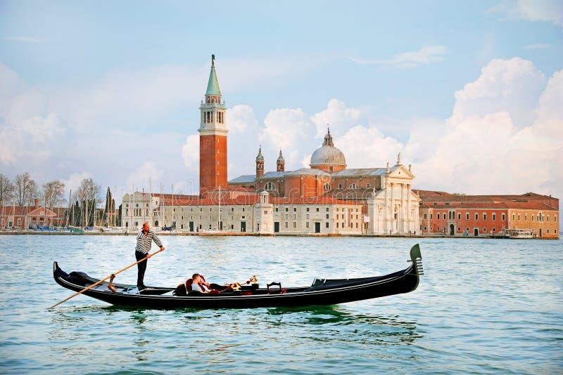 威尼斯,意大利- 2015年4月13日:传统长平底船美丽的景色在运河的重创与backg的圣乔治Maggiore教会 库存照片