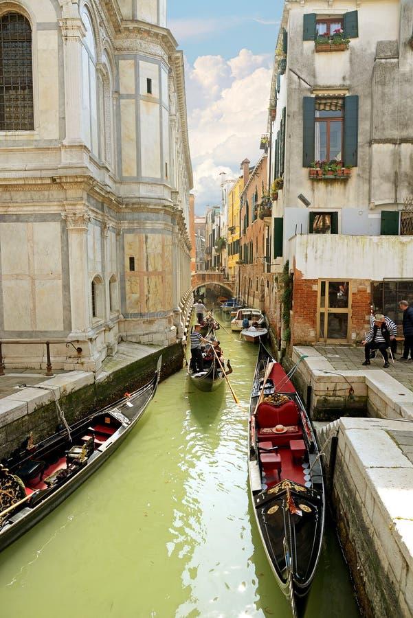 威尼斯,意大利2015年4月13日:美好的城市视图和典型的长平底船在狭窄的威尼斯式运河,威尼斯,意大利 被定调子的方形的图象 免版税库存图片
