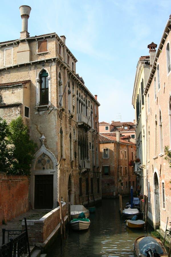 威尼斯,运河的古老房子有被停泊的小船的 图库摄影