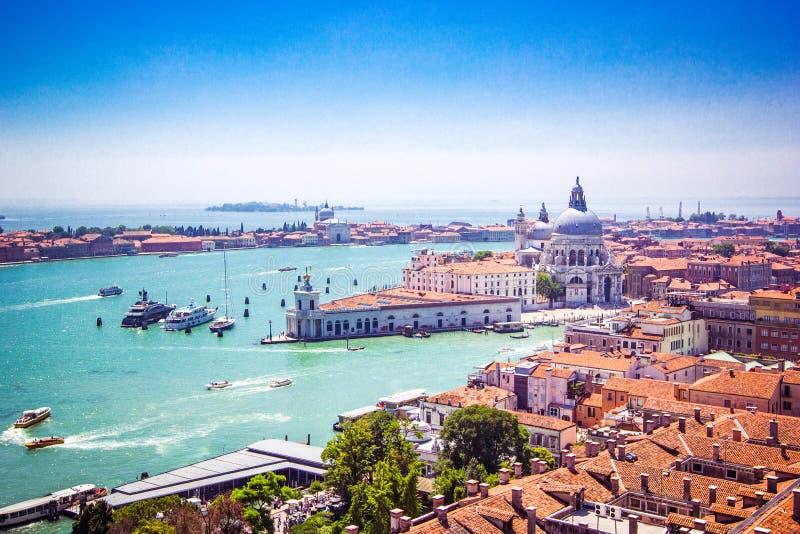 威尼斯-大教堂安康圣母圣殿,有长平底船和房子,威尼斯红瓦顶的大运河全景, 免版税库存图片