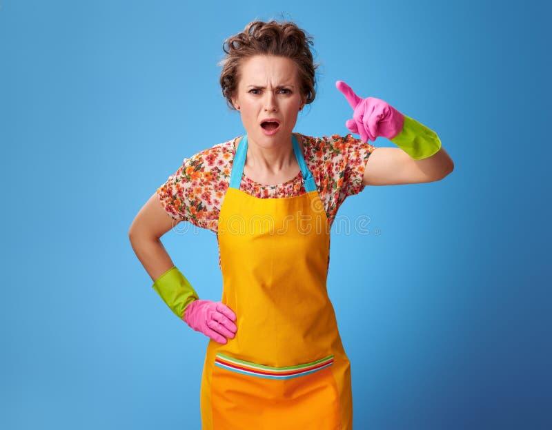 威胁与在蓝色的手指的懊恼年轻女人 库存图片