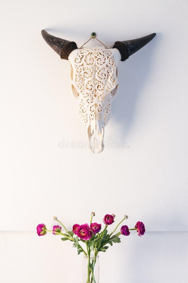 威胁与桃红色玫瑰家庭装饰内部的公牛头骨顶头装饰品 免版税库存照片