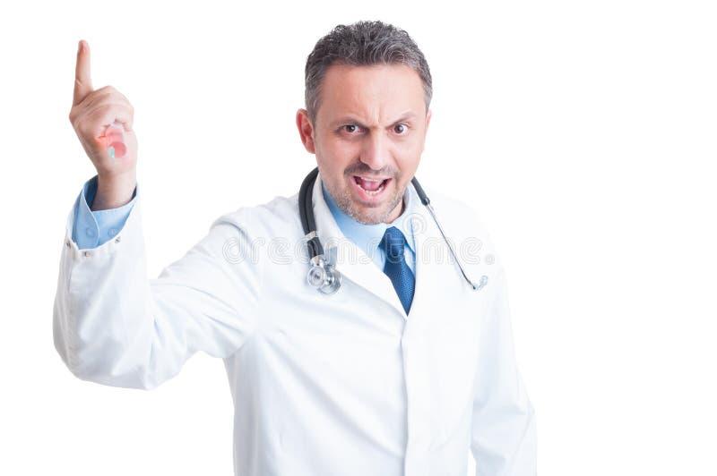 威胁与注射器的恼怒的积极的医生或军医 库存图片