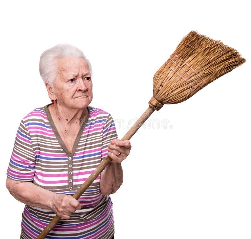 威胁与笤帚的老恼怒的妇女 免版税库存照片
