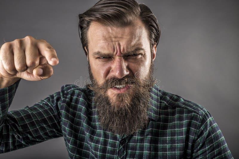 威胁与他的fi的一个恼怒的有胡子的人的特写镜头画象 免版税库存图片