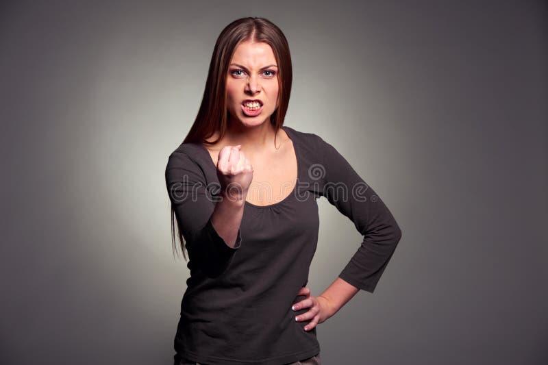 威胁拳头的恼怒的妇女 免版税库存照片