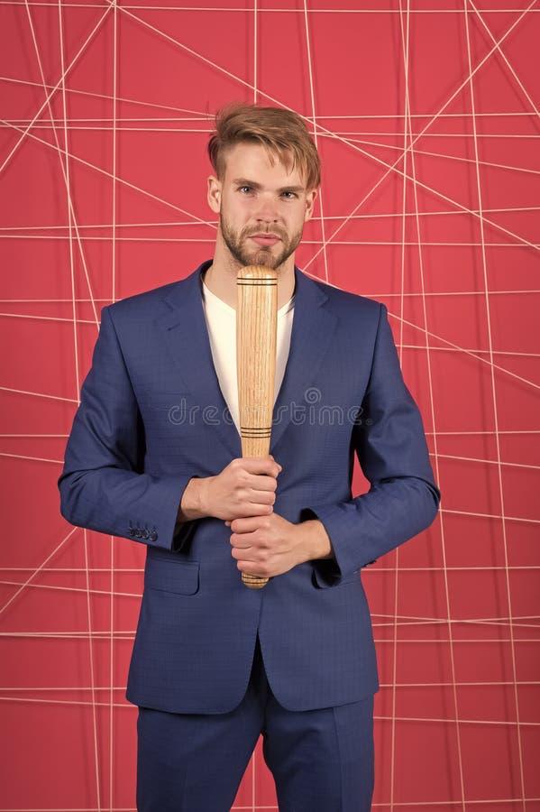 威胁的暴力 商人正式典雅的衣服桃红色背景 人举行木棒 有刺毛神色的人 免版税库存图片