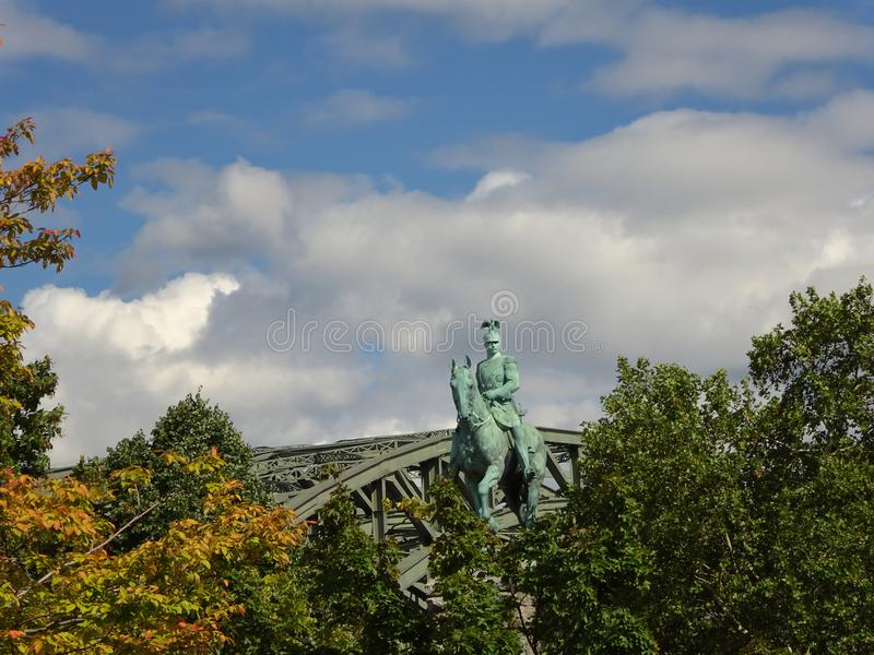 威谦廉雕象在桥梁前面的科隆 免版税库存图片