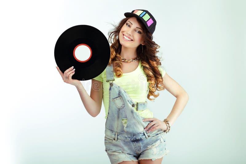 娱乐 举行唱片和微笑的滑稽的妇女 免版税库存图片
