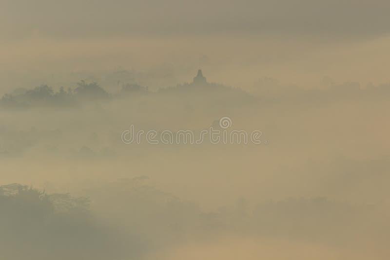婆罗浮屠寺庙在有薄雾的早晨如被看见从Punthuk Setumbu小山 图库摄影