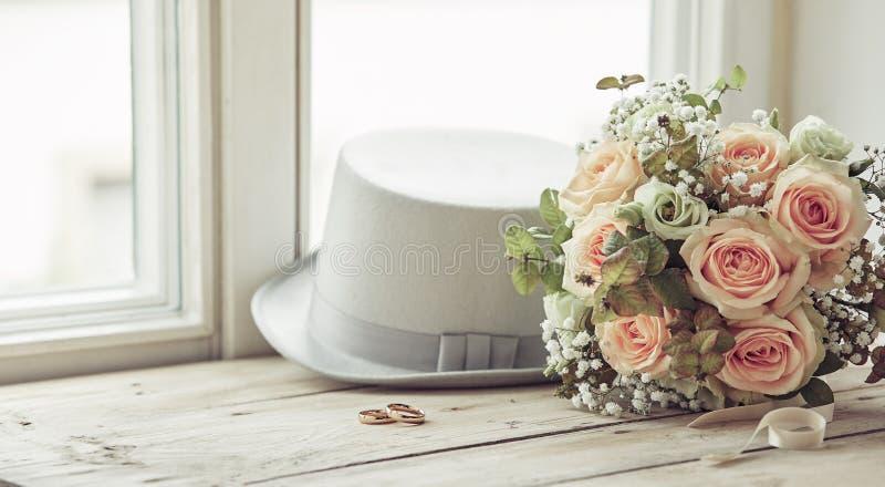 婚姻天结构的帽子、圆环和花束 库存照片