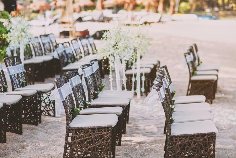 婚姻的地点的海滩婚礼木椅子安排沙子的 库存图片
