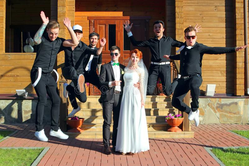 婚姻的夫妇和跳跃的新郎的朋友 库存照片