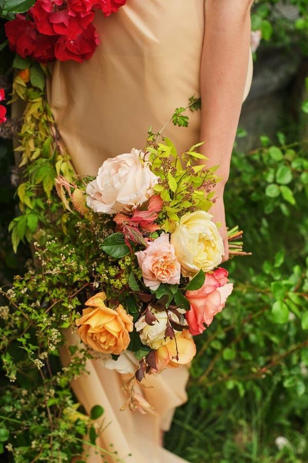 婚姻的摄影:举行美好的大白色的一丝绸婚纱的一个新娘,脸红,变粉红色,桃子,橙色婚姻的花束 免版税库存图片