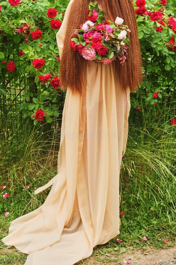 婚姻的摄影:举行美好的大白色的一丝绸婚纱的一个新娘,脸红,变粉红色,桃子,紫色婚姻的花束 免版税库存图片