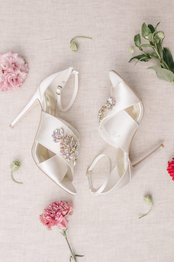 婚姻的桃红色花玫瑰和绿色,时髦的典雅的经典之作上漆了米黄鞋子和两个银婚圆环说谎 图库摄影