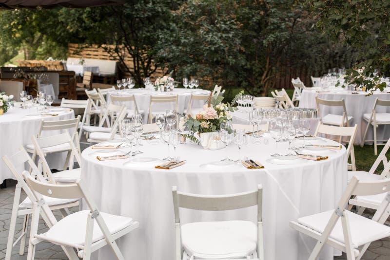 婚姻的桌设置用在一个黄铜花瓶的鲜花装饰了 ??floristry 户外客人的宴会桌与a 库存图片