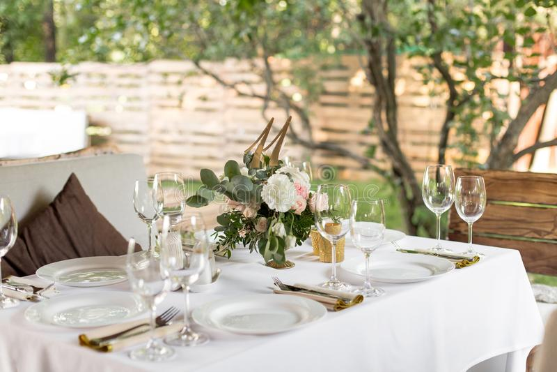 婚姻的桌设置用在一个黄铜花瓶的鲜花装饰了 ??floristry 户外客人的宴会桌与a 库存照片