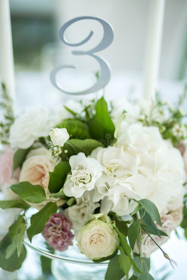 婚姻的桌设置用鲜花和白色蜡烛装饰 ??floristry 与玫瑰的花束,八仙花属和 免版税库存照片