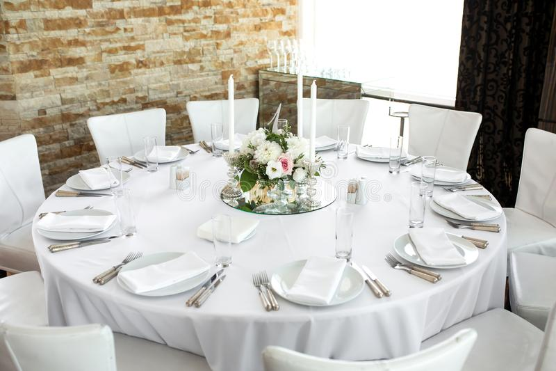 婚姻的桌设置用鲜花装饰了 白色板材、银器、白色桌布和绝尘室 ??floristry 库存照片