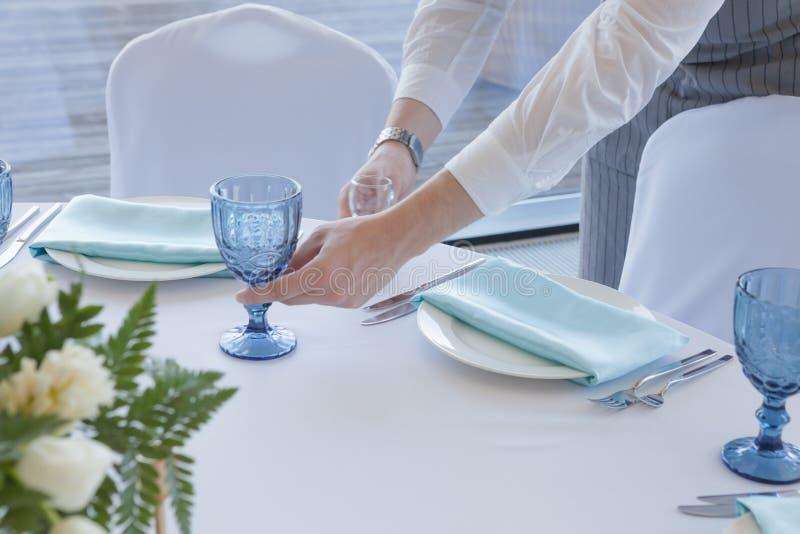 婚姻的桌设置 一灰色衣服和白色衬衫的侍者服务桌 图库摄影