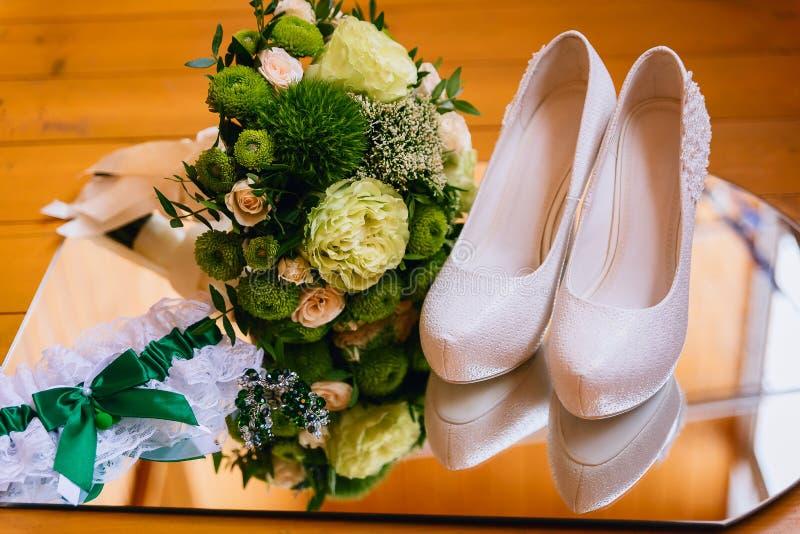 婚姻的细节、绿色新娘花束、鞋子、新娘袜带和耳环 免版税库存照片