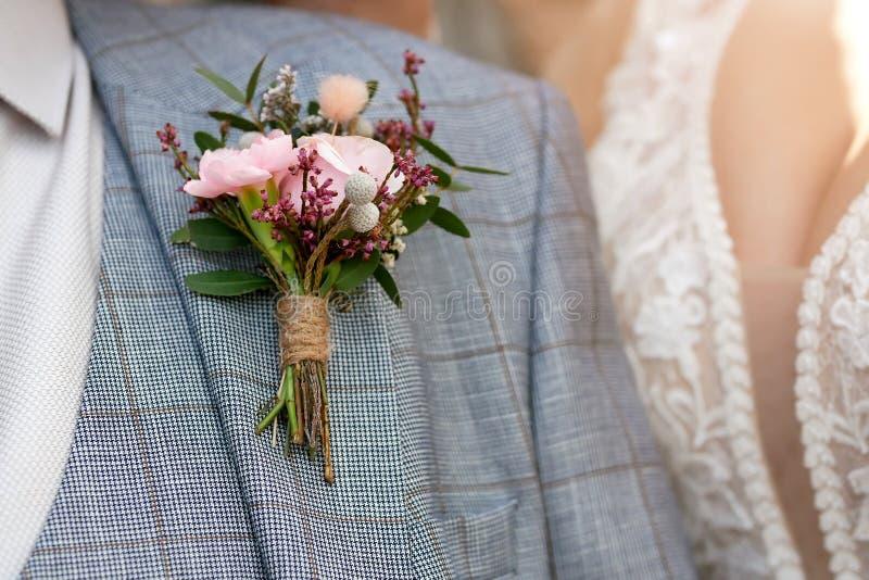 婚姻的背景,在新郎夹克的钮扣眼上插的花 库存照片