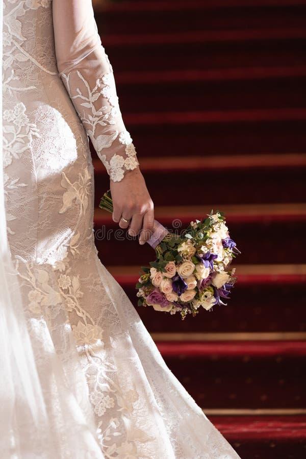 婚姻的花束在一个新娘的手上有红色台阶的在背景中 库存照片